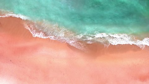 Aerial view of pink sand beach and sea. Looping ocean surface texture, Top view sea waves slow motion, flying over tropical sandy beach and waves, Sunset  beach seamles loop.
