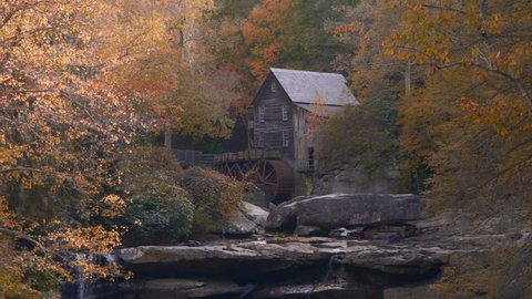 Beautiful cinematic tracking shot of Glade Creek Grist Mill in West Virginia near Clifftop in Babcock State Park on the first day of October in the Fall with Autumn leaves in flat picture profile.