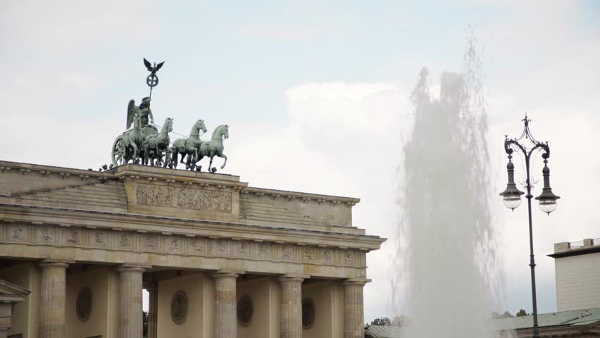 Famous tourist attraction in Berlin - Brandenburg Gate. A fountain and a street lamp. A summer day. Real time locked down medium shot
