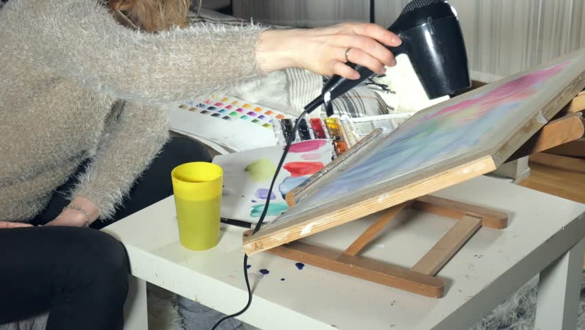 Adult women paint with colored watercolor paints and dry with a hair dryer in an art school 4k