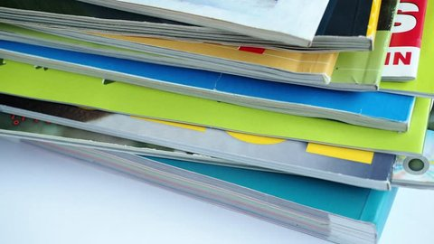 Magazines with selective focus on foreground edge. Edge stack of the colorful magazines
