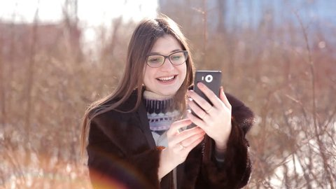 Beautiful girl in a snow-covered winter city using Skype on a smartphone communicates with his family