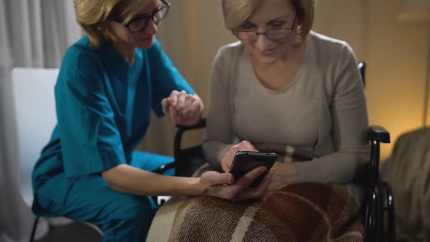 Friendly volunteer teaching woman in wheelchair to use smartphone, nursing home
