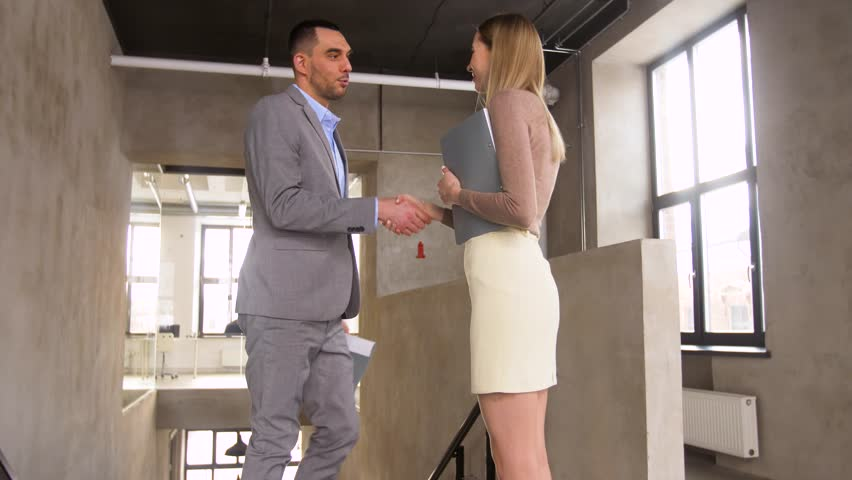 Business, people and corporate concept - happy smiling businessman with folder walking upstairs, meeting and greeting businesswoman by handshake at office | Shutterstock HD Video #1009142048