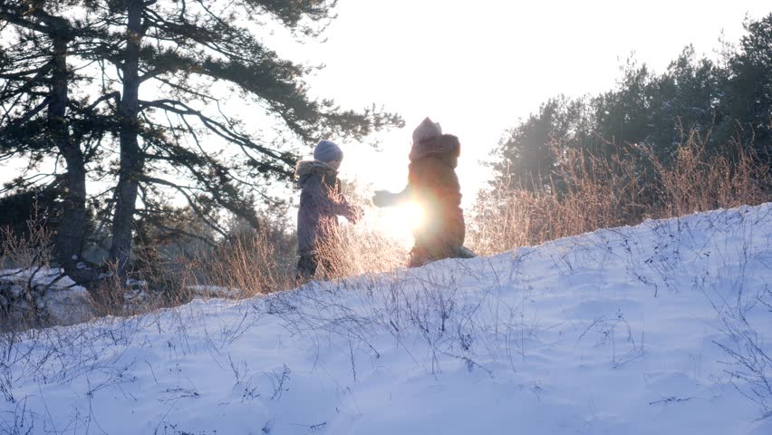 Happy winter rest, mom plays with son in backlight on snow at forest on background of beautiful nature   Shutterstock HD Video #1009164278