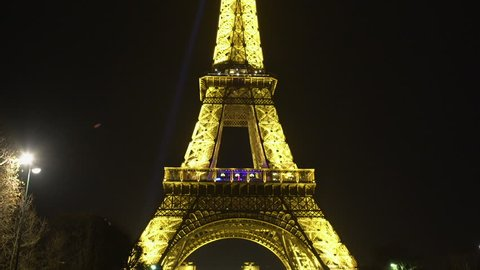 PARIS, FRANCE - CIRCA JANUARY 2016: Sightseeing in the city. Bright lighted Eiffel Tower against dark night sky background in Paris, zoom in