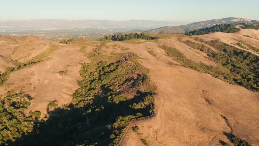 Aerial footage of picturesque hills, meadows, and forests in California. The sun is shining and making the whole scene orange and warm. | Shutterstock HD Video #1009168688
