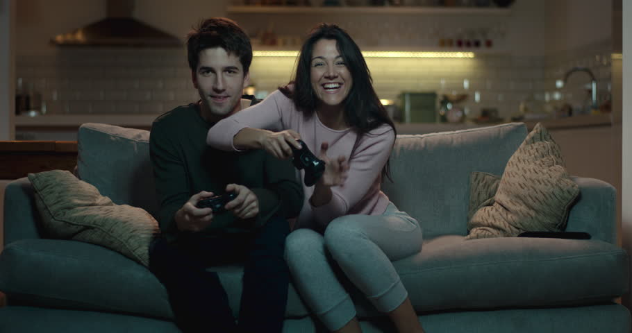 Competitive couple push and shove each other as they play a video game at home