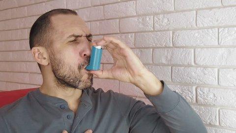Asthma. A man with an inhaler.