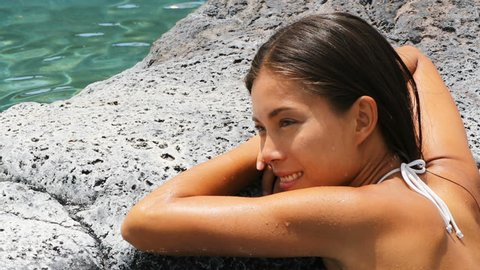 Spa wellness - woman relaxing in hot tub whirlpool jacuzzi outdoor at luxury resort spa retreat. Happy young mixed race Asian Caucasian female model relaxed resting in water near pool on vacation.