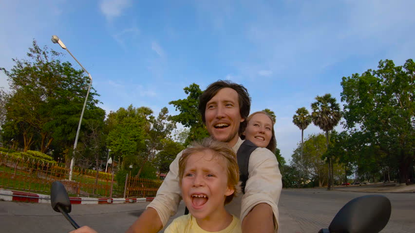 Slowmotion shot of a family doing selfie riding on a motorbike in front of a Wat Chalong buddhist temple on Phuket island, Thailand