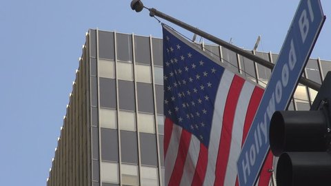 Famous Hollywood avenue traffic sign by day, American flag wave in Los Angeles