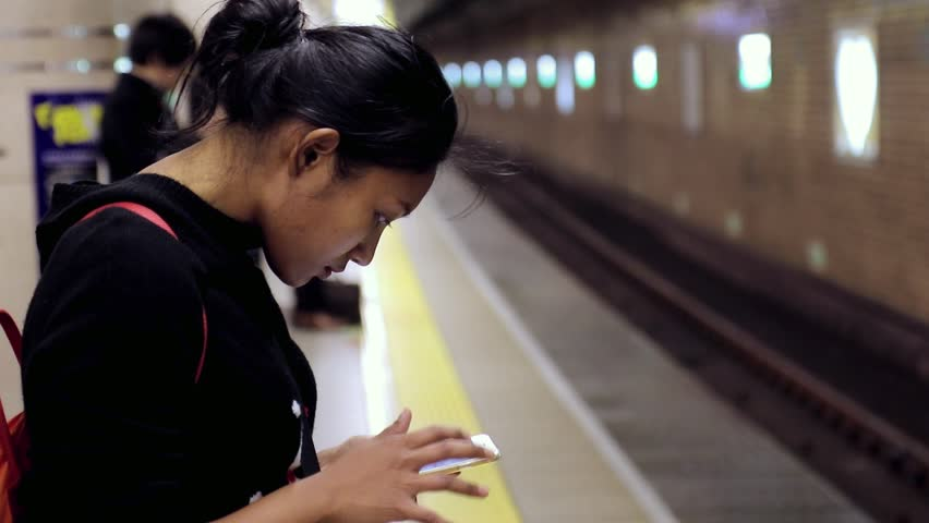 A young woman in a subway using her cell phone. The girl waits for the train and touches the mobile phone. Internet connection on the railway station, Tokyo, Japan.