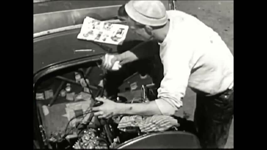 CIRCA 1950s - A schoolboy works on his hotrod while reading Hot Rod magazine and, after a test run at the racetrack, he checks his engine.