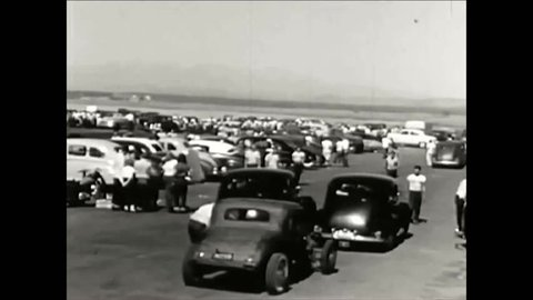 CIRCA 1950s - A couple driving a car after a jalopy enter a racetrack for hotrods, motorcycles and stock cars in Santa Ana, California, in 1952.