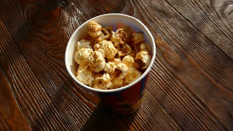 Pop corn in a paper glass. Take the hand and eat pop corn.