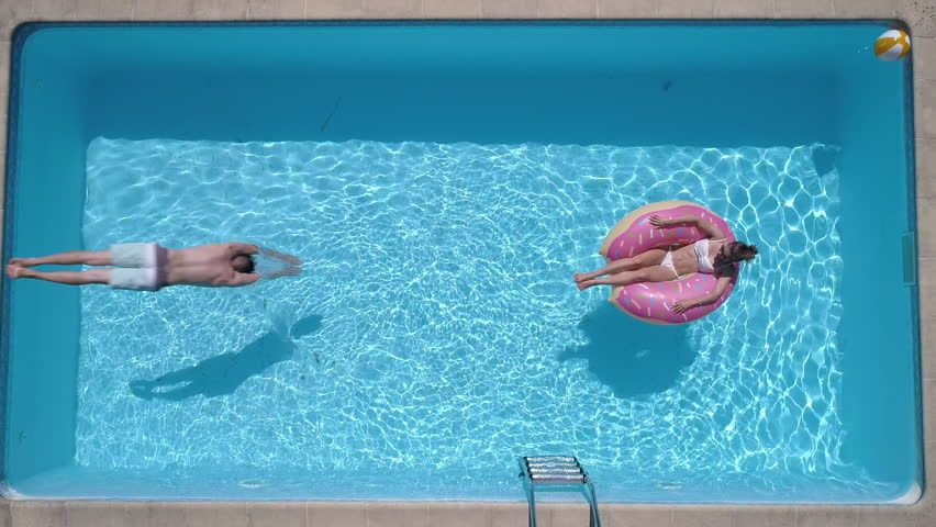 Aerial - Adult man dives into the the pool while girl is lying on a donut pool float (slow motion) #1009227818