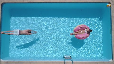Aerial - Adult man dives into the the pool while girl is lying on a donut pool float (slow motion)