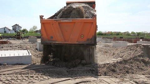 Dump truck is unloading soil. Dumper truck is unloading soil or sand at construction site.