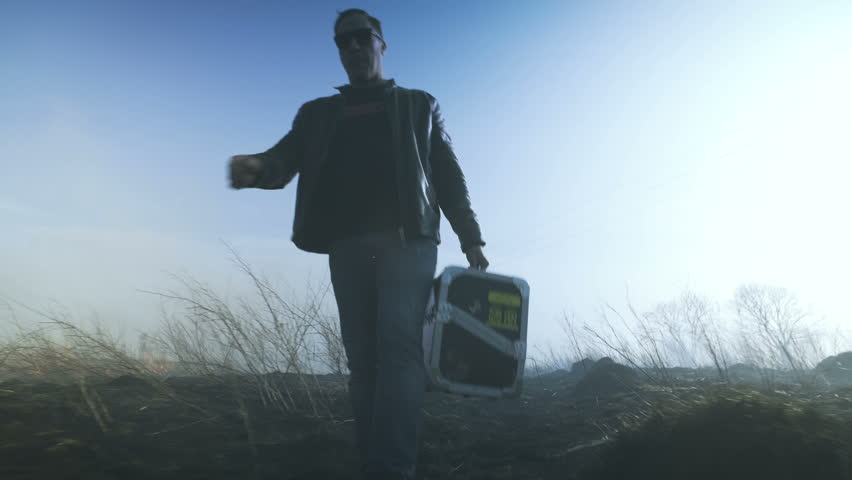 A man with a case is walking along a burning field. 4k #1009244588