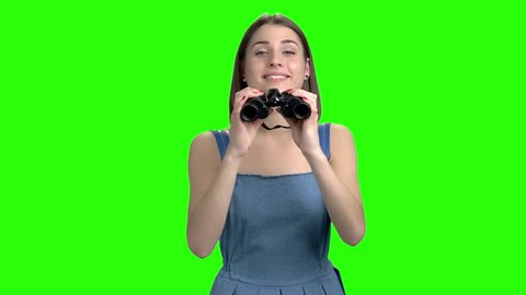 Teen girl use binoculars, front view. Portrait of woman in denim dress looks throug binocular. Green screen hromakey background for keying.