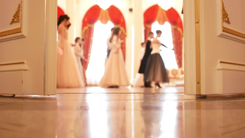 Young men and women in vintage fluffy dresses dancing waltz