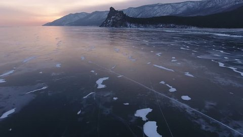 Cinematic Deep cracks Lake Baikal Transparent blue colorful smooth waterside ice iceberg. Mountains sharp rock pine trees forest. Cinematic Best Russia Arctic. Winter orange sunrise. Aerial Approach