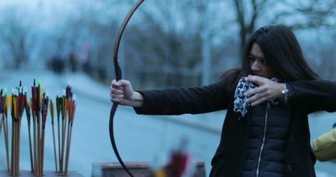 8f0d44c392d Woman archer shoots with a bow in 4K. Tourist woman practicing archery and  smiles to