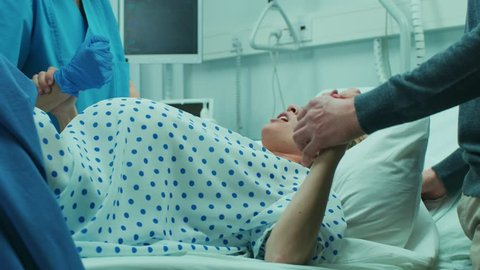 In the Hospital, Close-up on a Woman in Labor Pushing Hard to Give Birth, Obstetricians Assisting, Spouse Holds Her Hand. Modern Maternity Hospital with Professional Midwives. Shot on RED EPIC-W 8K.