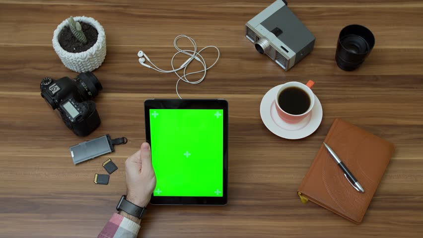 Top view on the office desk and black tablet computer with green screen and male hands taping and scrolling on it. Photo camera stuff and coffee beside. Vertical. Tracking motion. Chroma key. | Shutterstock HD Video #1009295768