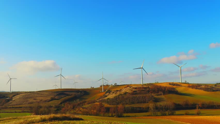 Wind turbines in the open field twist blades in the wind in the background of a blu sky. | Shutterstock HD Video #1009339808