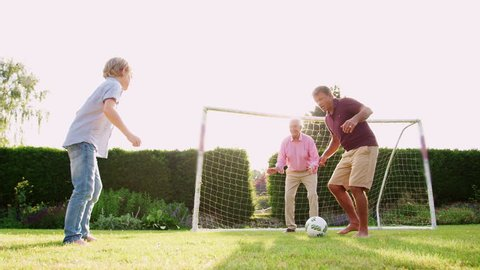 Three male generations of a family playing soccer in garden