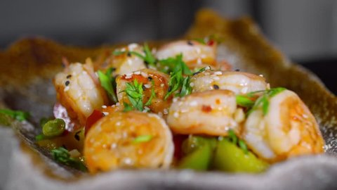 Close up of spinning plate with delicious shrimp and vegetables salad with sesame seeds