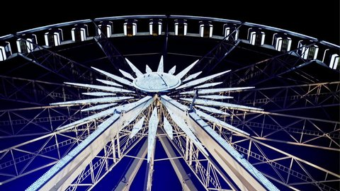 Rotating illuminated ferris wheel from below with passenger gondolas suspended on the rim against a night sky at a carnival or funfair.