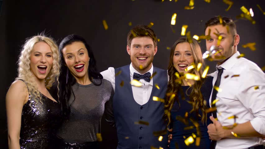 Celebration, people and holidays concept - happy friends at party under golden confetti over black background | Shutterstock HD Video #1009381118