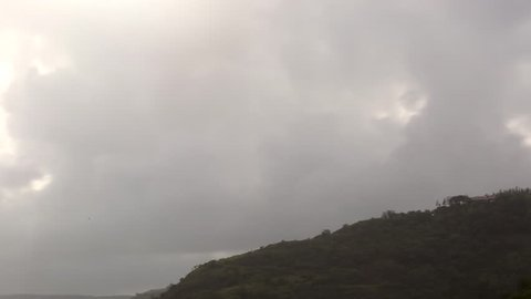 A stupendous time lapse of clouds passing west over a hill.