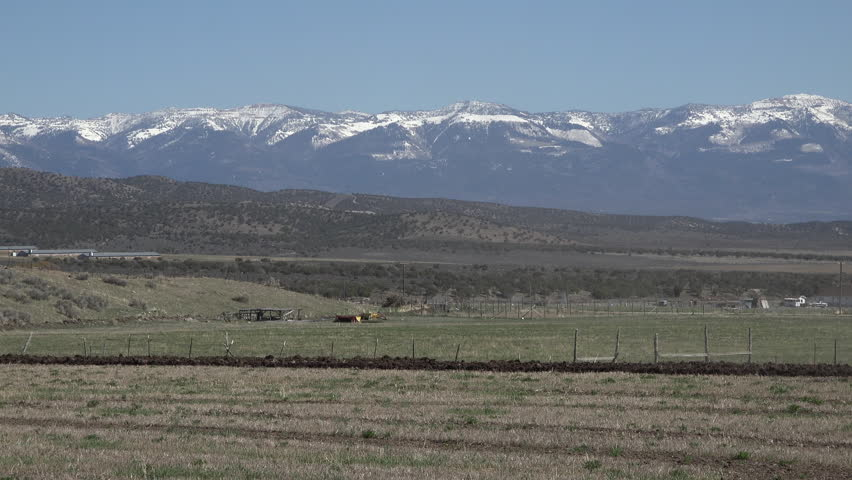 FOUNTAIN GREEN, UTAH - APR 2015: April farmer tractor plow field for spring planting. Heavy duty tractor in rural community plowing a field to prepare it for spring planting. Agriculture work labor.   Shutterstock HD Video #10093988