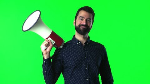 Handsome man with beard holding a megaphone on green screen chroma key