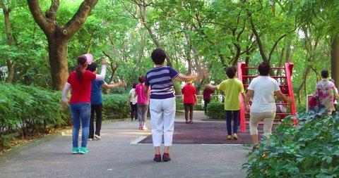 HONG KONG, CHINA - CIRCA 2017 - Chinese seniors practice tai chi in a park in the early morning in Hong Kong, China.