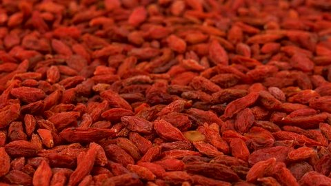 Full frame background of organic dried goji berries rotating on turn table. Loopable. Close up macro. Angled view.