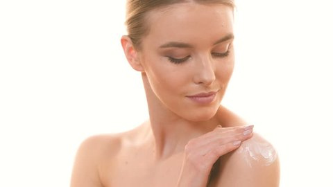 The cute woman applying a cream on the skin on the white background