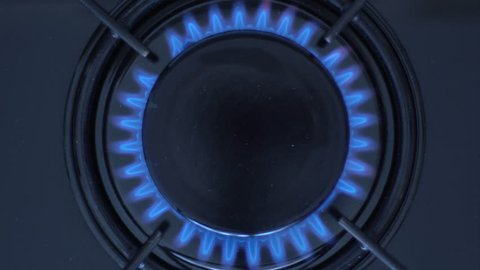 Kitchen burner turning on.Stove top burner igniting into a blue cooking flame.  Natural gas inflammation, close up.