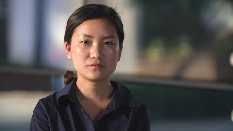 Portrait of Young asian woman looking at camera with Blank Expression in slow motion with dark office building background