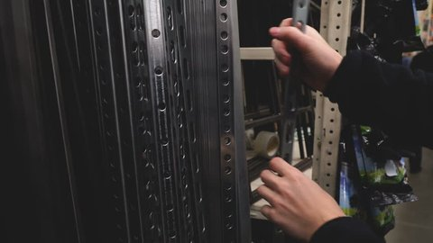 Man buying construction materials for making racks or furniture at store 4k