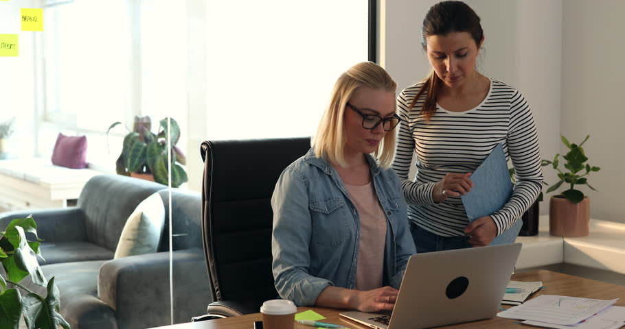 Two young businesswomen talking together over a laptop while working at a desk in a modern office | Shutterstock HD Video #1009474418