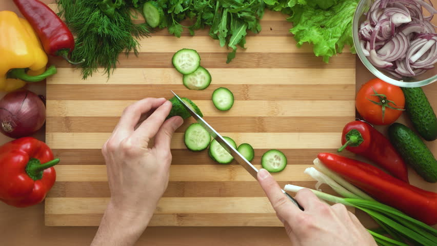 Top shot of man chef cutting cucumber on chopping wooden board | Shutterstock HD Video #1009501478