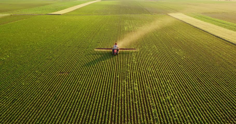Aerial drone shot of a farmer spraying soybean fields #1009501748