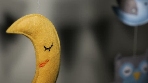 baby mobile with blue hand-stitched animal and bird toys with yellow moon on white wall background