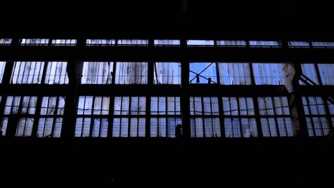 View to blue sky through the windows of old grungy industrial building