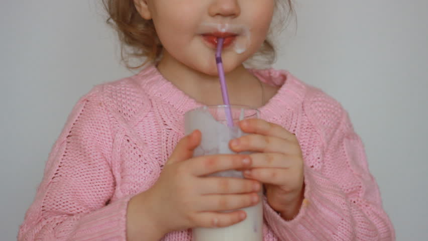 The child drinks a milk drink - kefir, smoothies, cocktail, yogurt. A nice little girl holding a glass in her hands and drinking through a straw